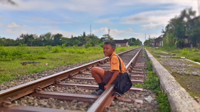 One boy sitting on a railroad